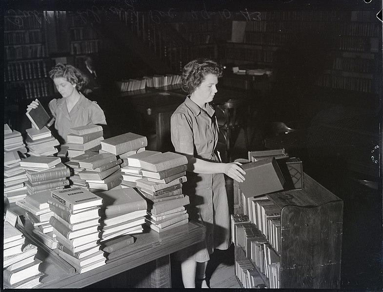 Foto de dos mujeres bibliotecarias ordenando libros.